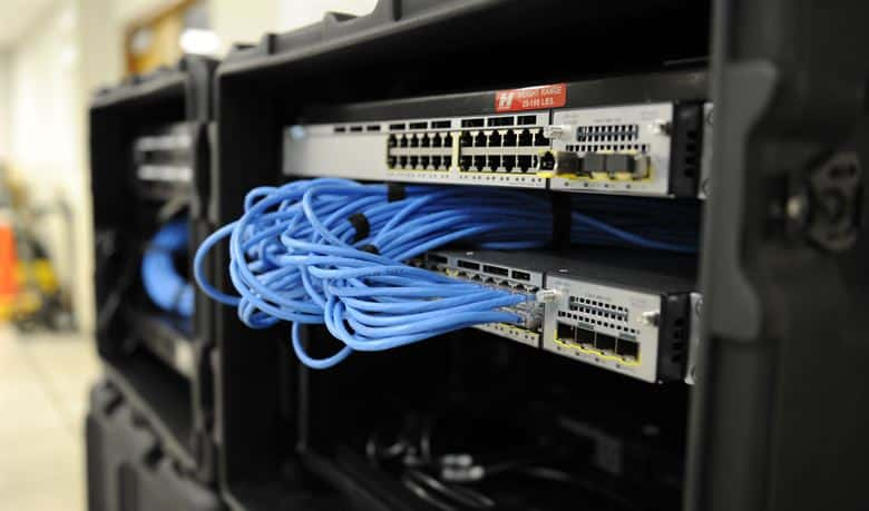 Shows a black cabinet with network switches and blues cabling