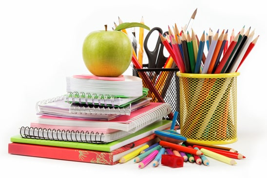 A stack of books on a desk with coloured pencils and a green apple